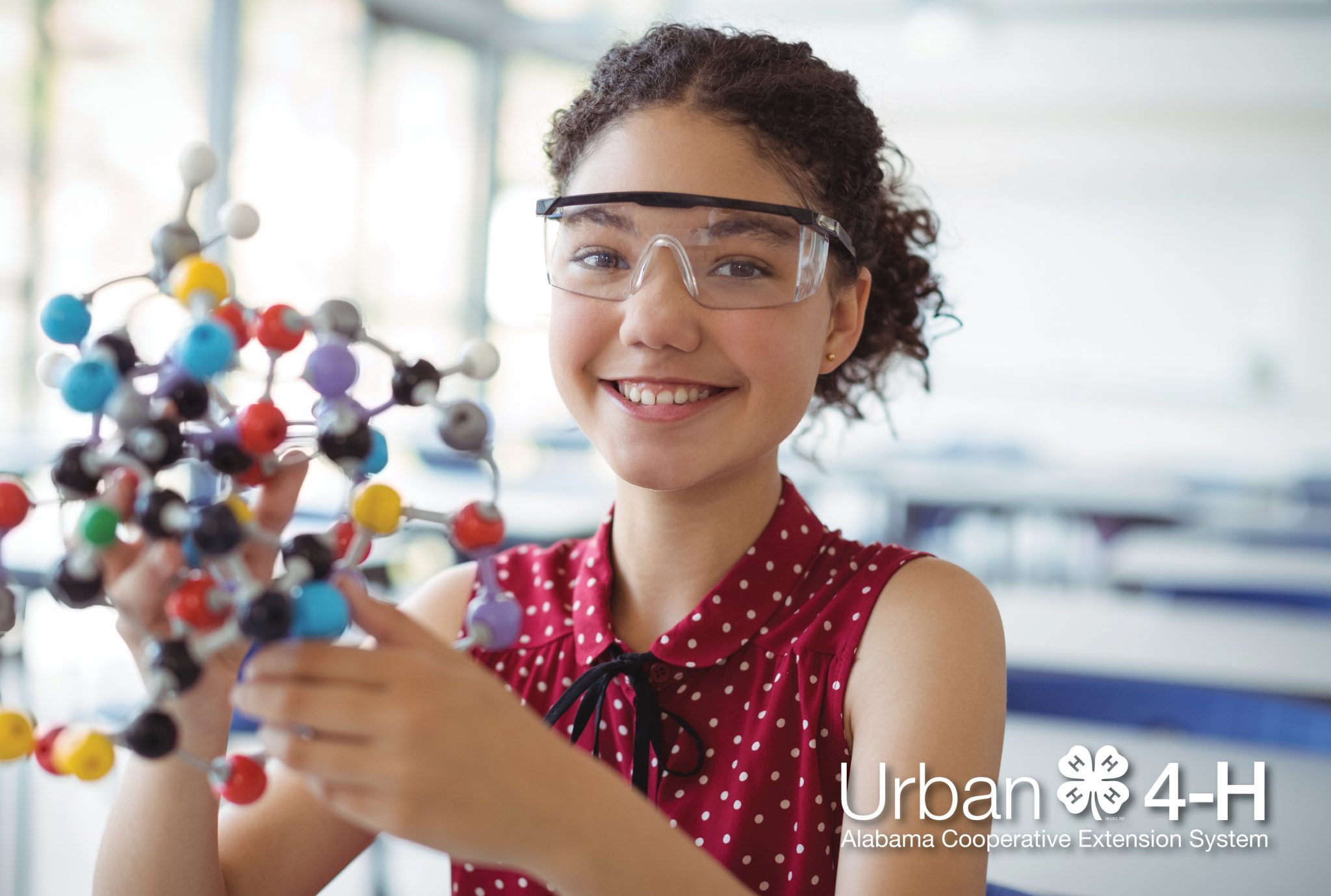 Middle School aged girl wearing safety goggles and holding a molecular model.