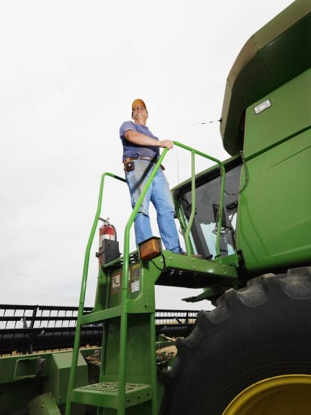 Farmer Standing on a Harvester