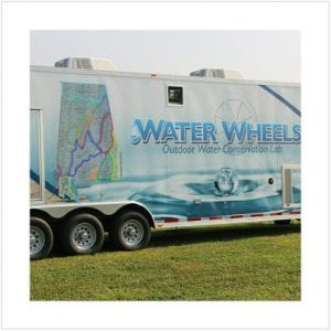 Side view of the exterior of the large trailer that is the mobile water wheels conservation laboratory.