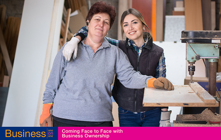 Two women carpenters stand inside their business workshop