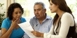 Senior Latino Couple Talking With Financial Advisor At Home