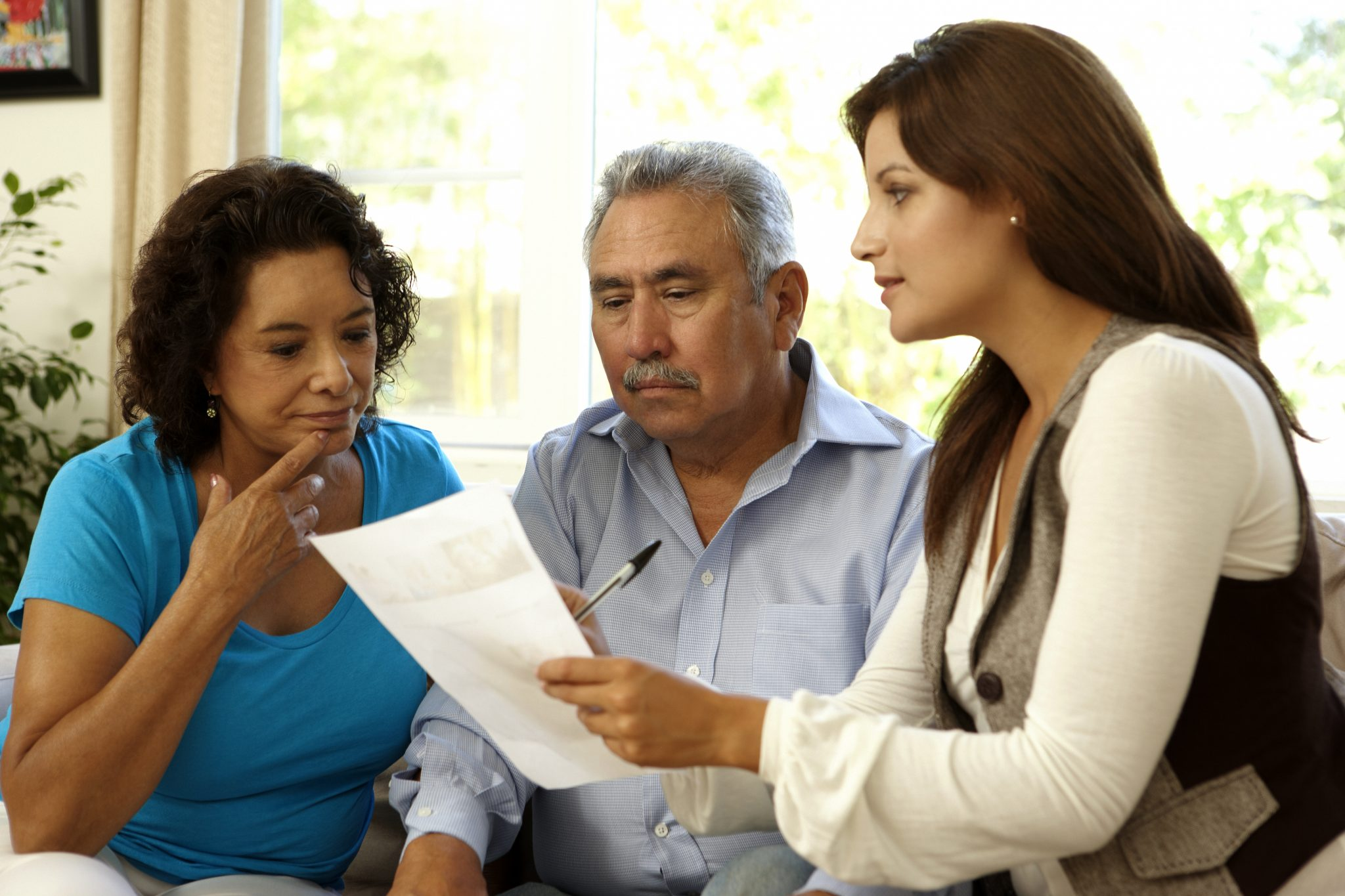 Senior Latino Couple Talking With Financial Advisor At Home
