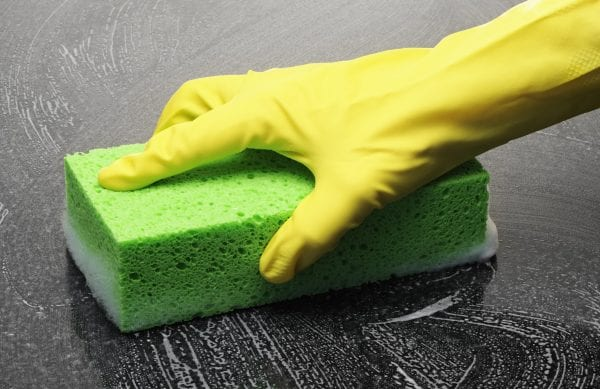 Cleaning a shiny surface with sponge and rubber gloves