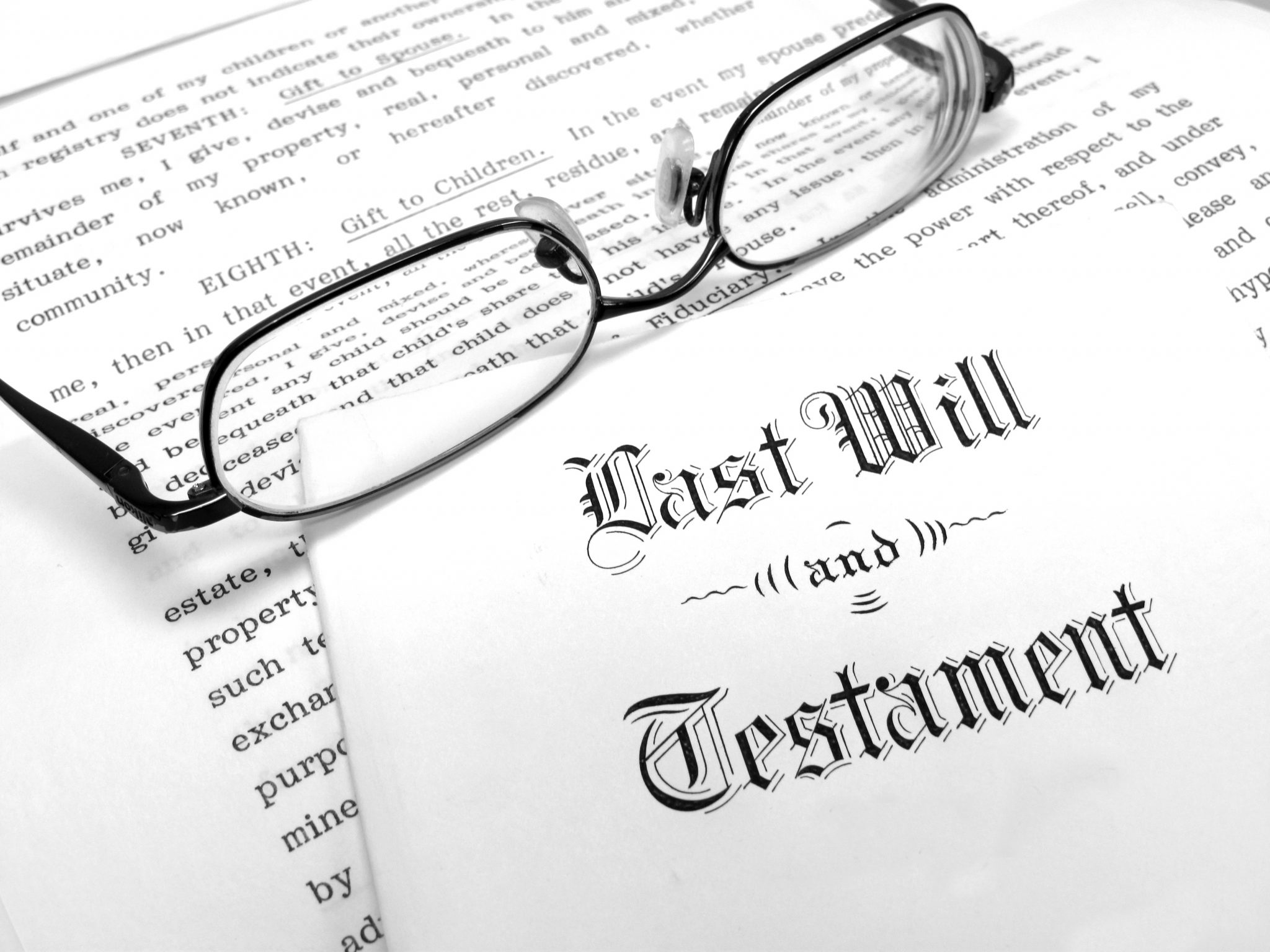 """A white envelope with text reading """"Last Will and Testament"""" lying on top of a white document with black text. A pair of black wire-rimmed reading glasses rests on the document. The black eyeglasses cast a shadow on the document."""