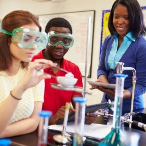 High school students Carrying Out Experiment In Science Class Wearing Protective Glasses