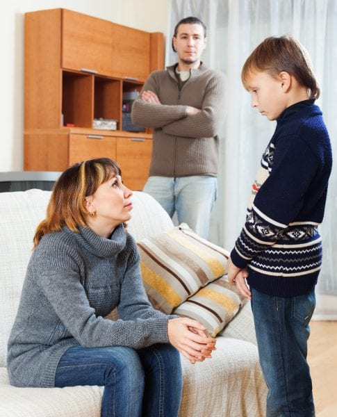 Mother and father scolding teenager son at living room