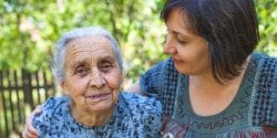 Middle aged Latino woman caregiver posing with her aging mother in the garden