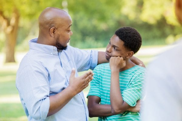 An African American father stands outdoors with his teenage son and places a hand over his shoulder as he gestures and shares some bad news. An unrecognizable person looks on as the son listens to his father with a gesture of disappointment.