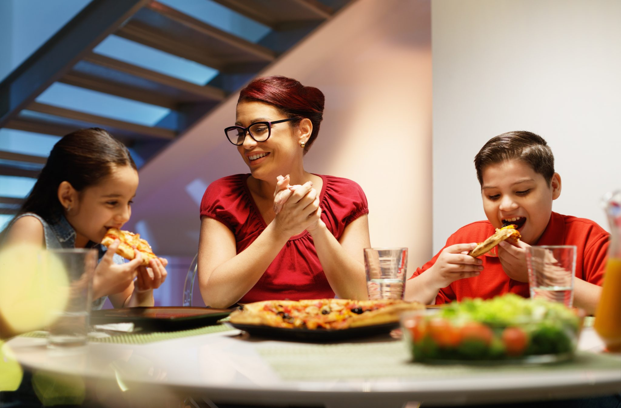 Hispanic family with mom, son and daughter having dinner at home and eating homemade pizza. Latino people with mother, boy and girl during meal.