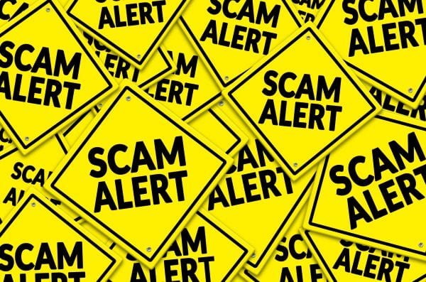 Scam Alert written on multiple warning road sign