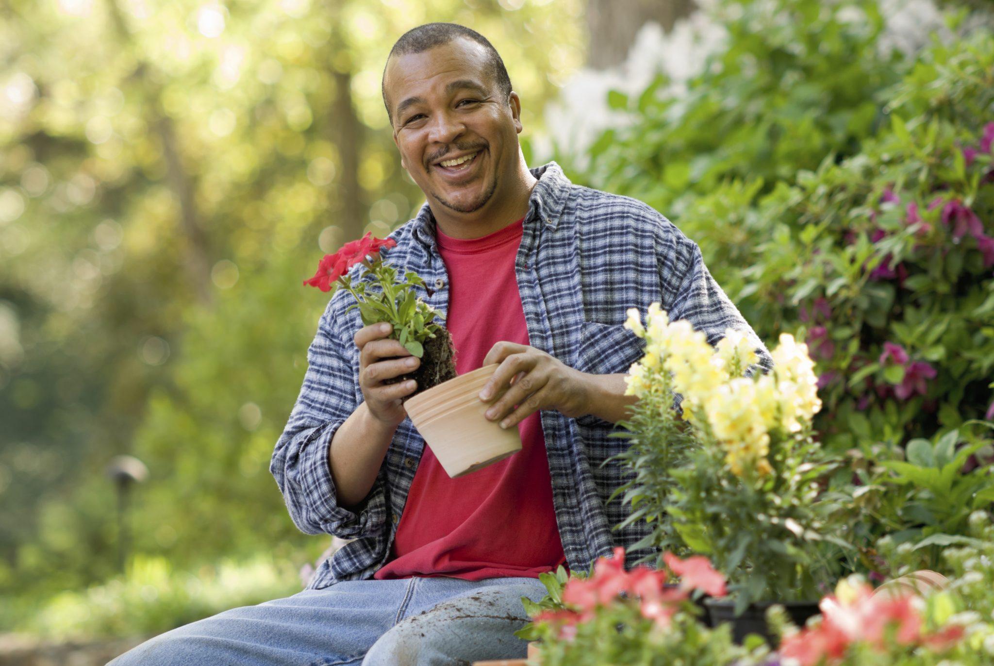 Black man sitting in a garden