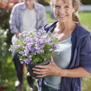 A smiling woman holding potted flower in garden