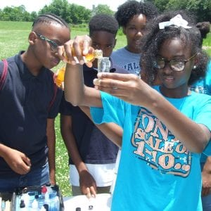 A group of students participating in water chemistry observations. A girl holds a tube of water as she pours in a solution