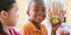 EFNEP impacts; Kindergarten children eating lunch smiling at camera