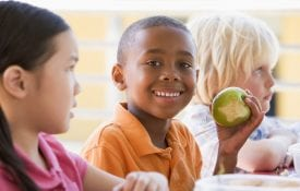 EFNEP impacts; Kindergarten children eating lunch smiling at camera