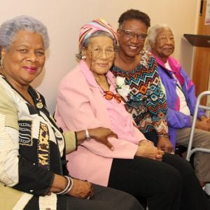 Four older women sit in a row, smiling for the camera