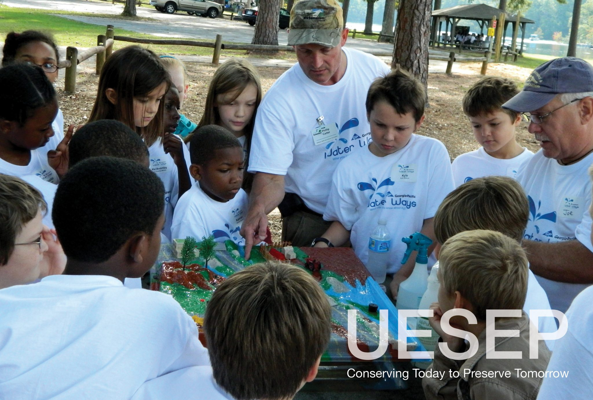A group of elementary school aged children gather around a water cycle model