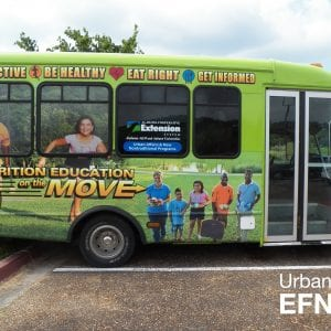 The side of the Nutrition Education on the Move Bus parked in a parking lot.