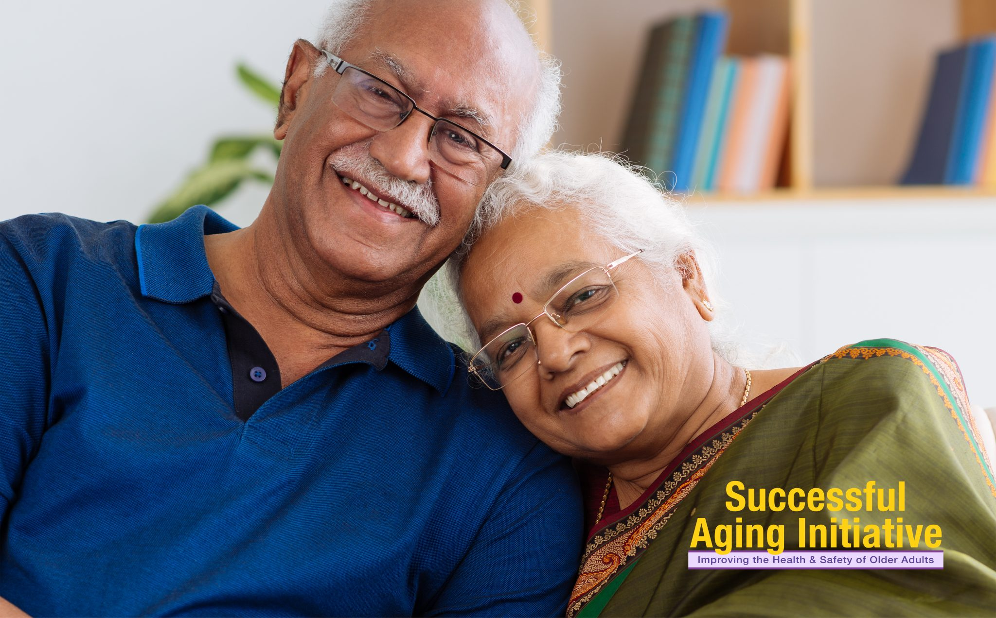 An Indian American older adult couple sits on their sofa, smiling.