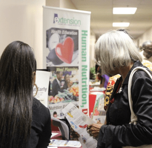 One older African American woman and one younger woman look over an information booth at an SAI conference