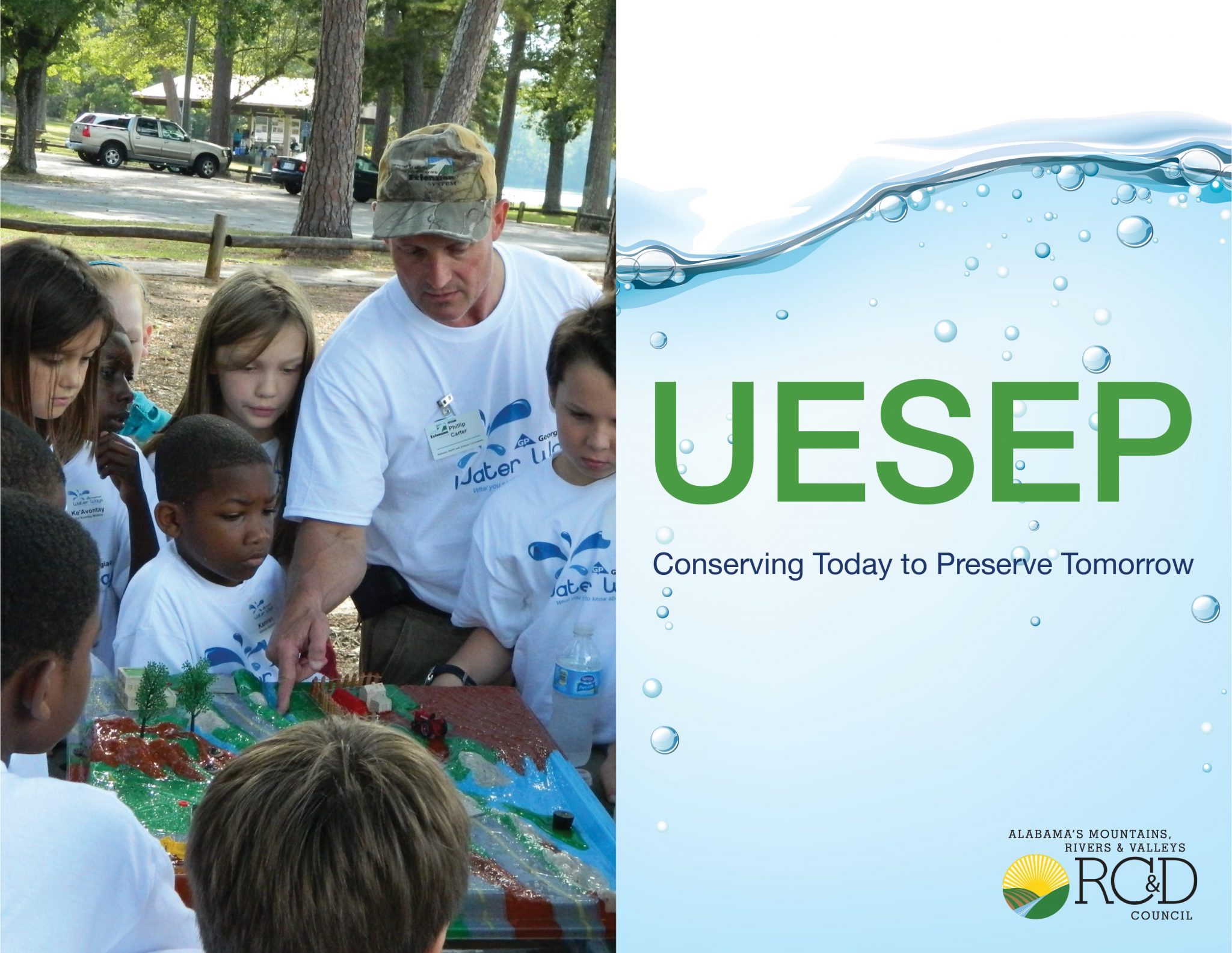 A group of elementary age children interact with a water conservation demonstration.