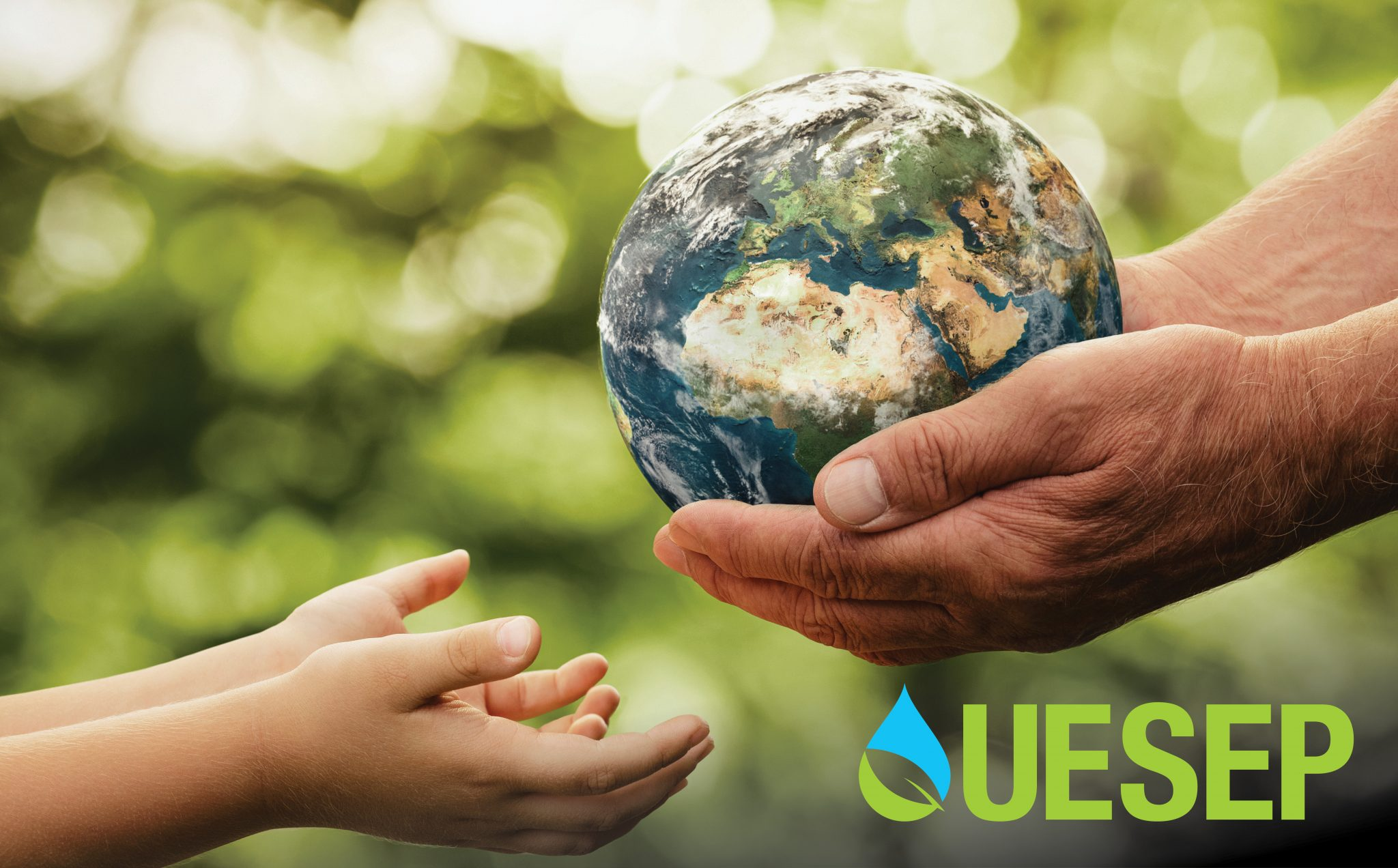 Close-up of the hands of an older adult passing the earth down to a child.