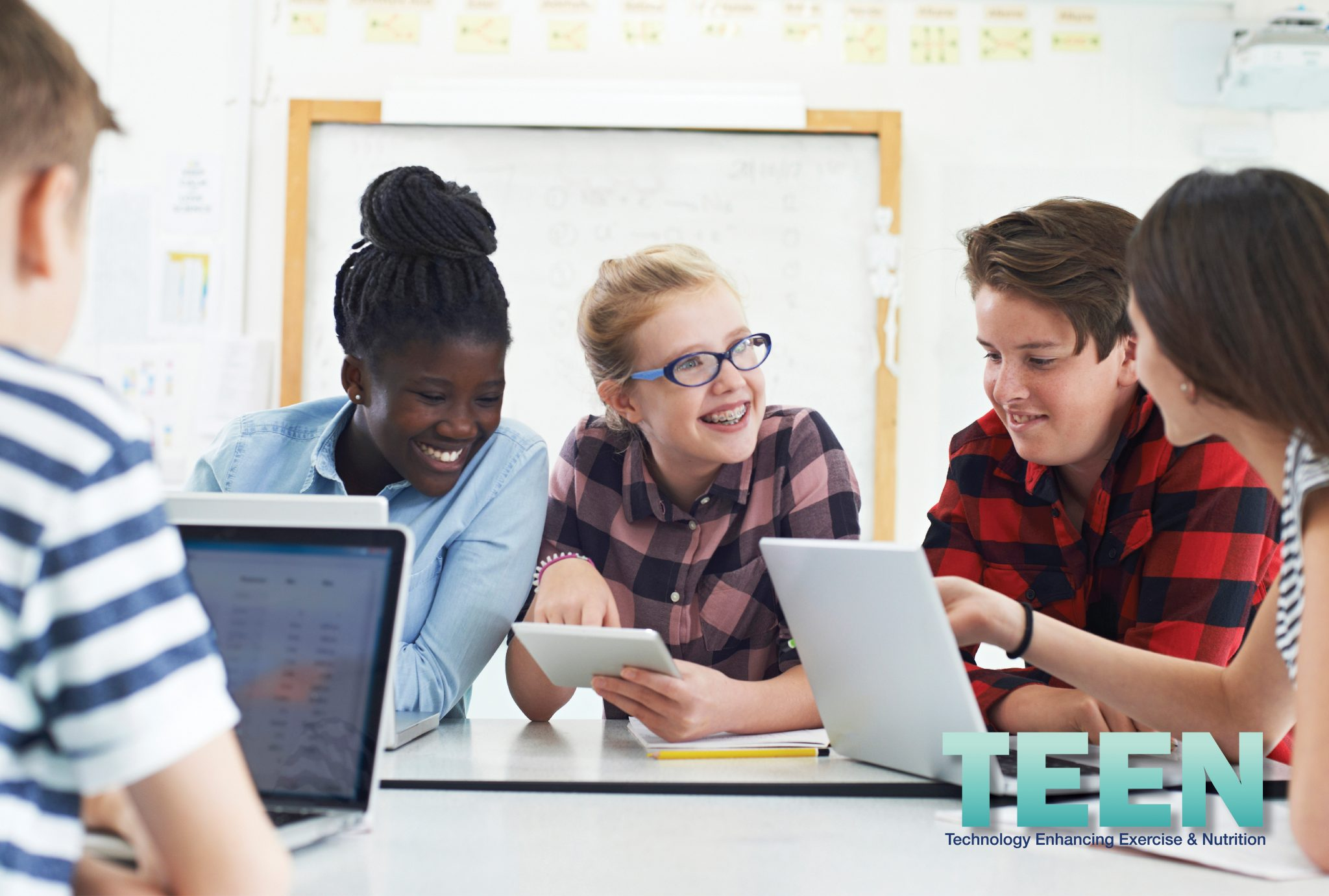 Group of diverse middle school kids have a discussion while looking at computer screens.