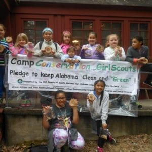 Girl Scouts pose beside the Camp Conservation Banner
