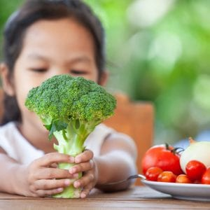 Cute asian child girl holding broccoli and learning about vegetables