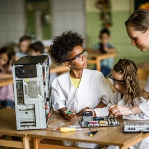 Female teacher teaching school girls how to repair electrical components on a class in the classroom. Focus is on black girl.