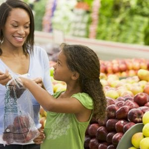 African American mother and daughter in supermarket produce section