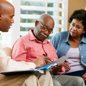 Two senior adults sit with a financial advisor looking over their estate paperwork