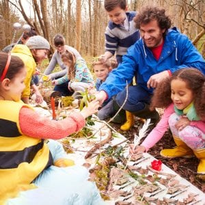 Group of elementary children gather things found in nature to study with two teachers.
