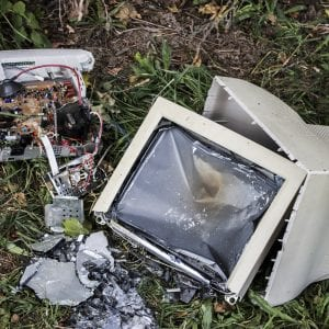 broken white computer lying on the grass