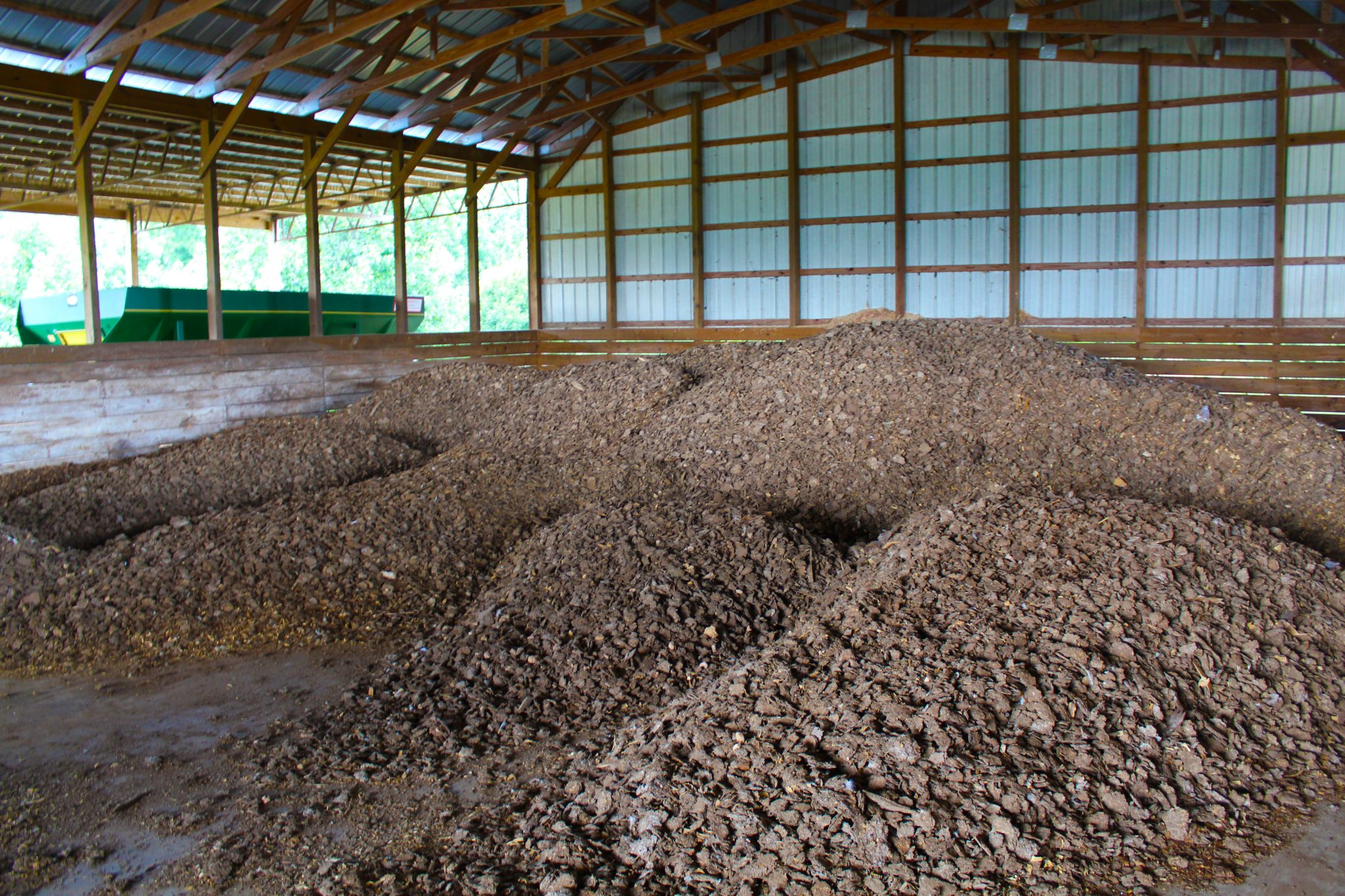 Figure 1. Broiler litter inside a poultry mega-house (left) and caked litter stored in a dry-stack barn (right)