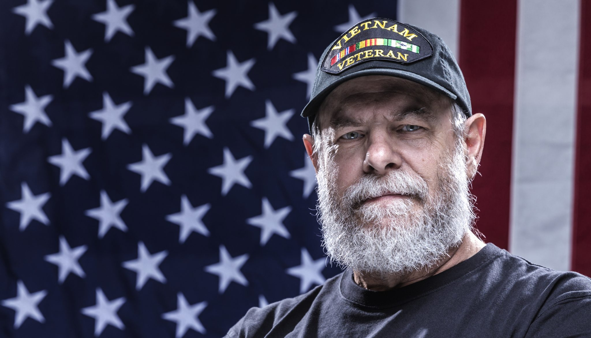 Close-up headshot of an authentic 67 year old United States Navy Vietnam War military veteran looking at the camera.
