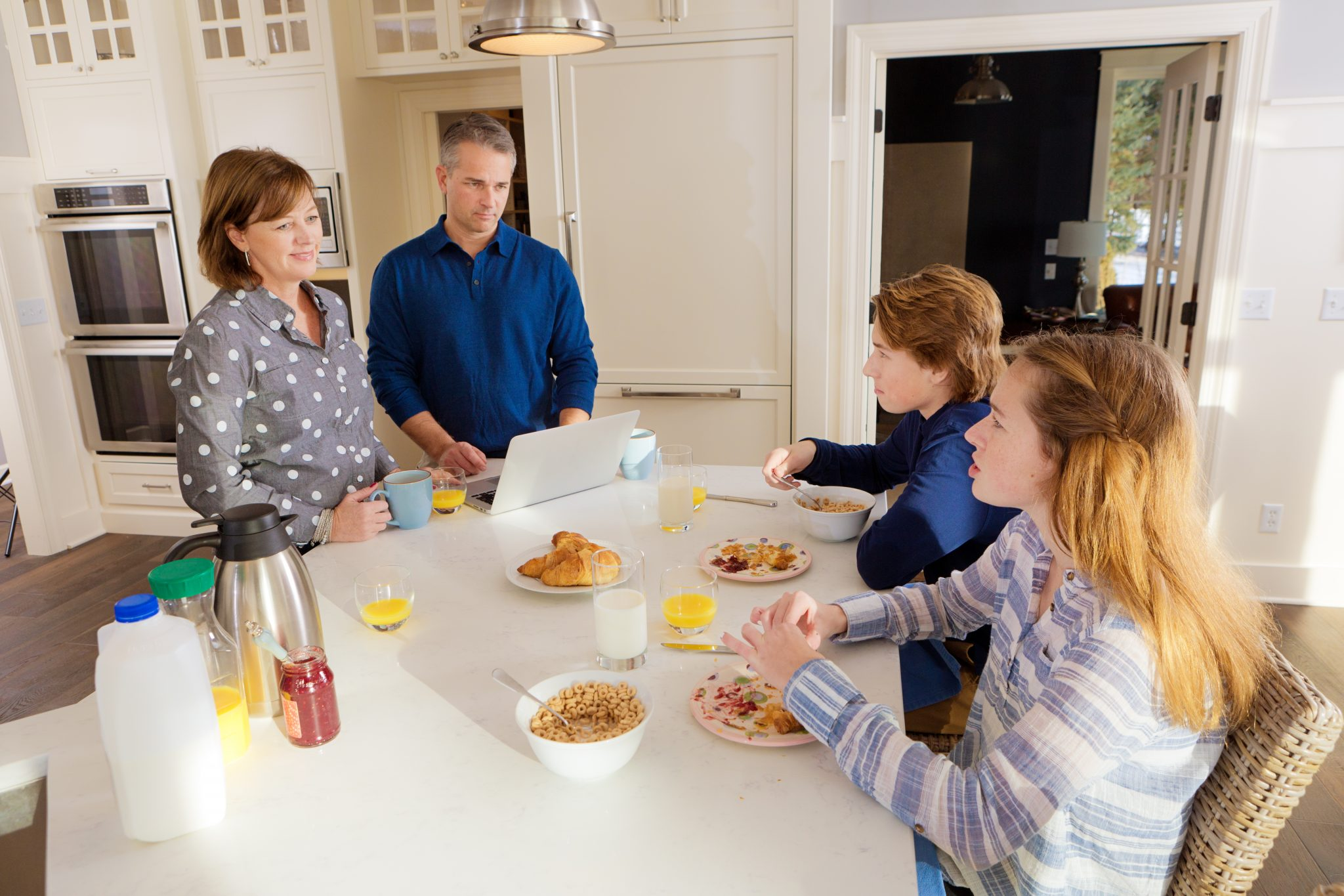 A Caucasian family with two parents and two teenage children doing breakfast at the family kitchen counter, dad is working in his laptop computer, the children is having morning breakfast.