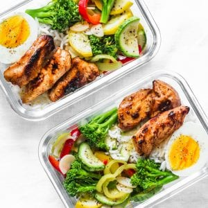 Rice, stewed vegetables, egg, teriyaki chicken - healthy balanced lunch box on a light background, top view