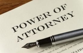 A power of attorney document on a desk with a pen.