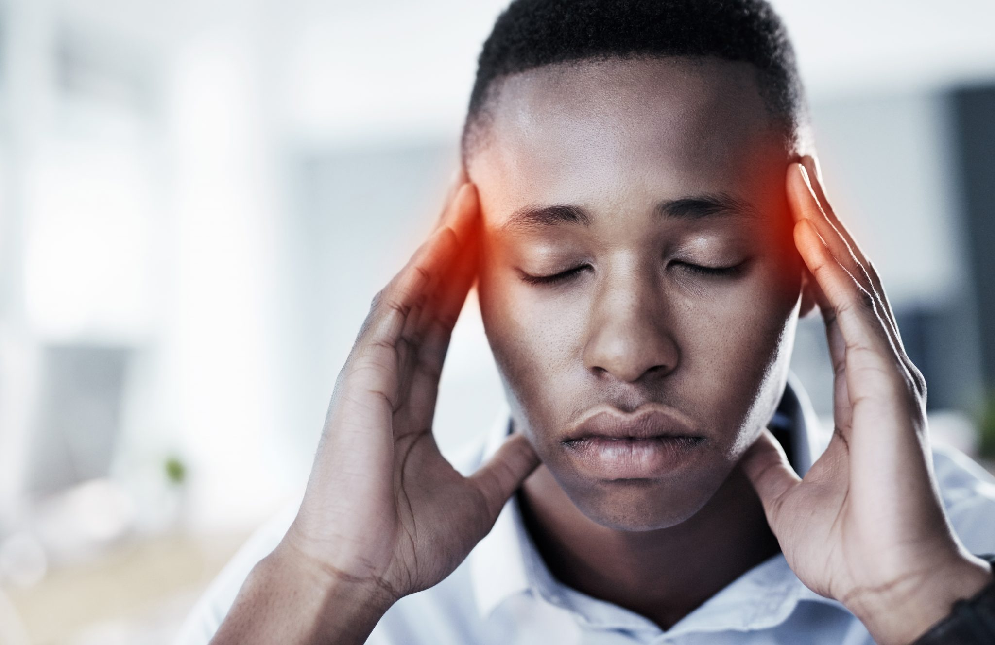 Shot of a young and stressed businessman suffering from a headache while trying to work in the office