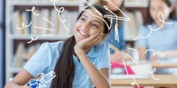 Pretty middle school girl smiles while daydreaming about her future. She is sitting in a class room.