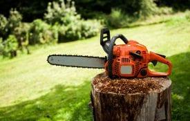 Chain saw sitting on a stump.