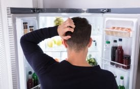 Rear View Of A Confused Young Man Looking At Food In Refrigerator