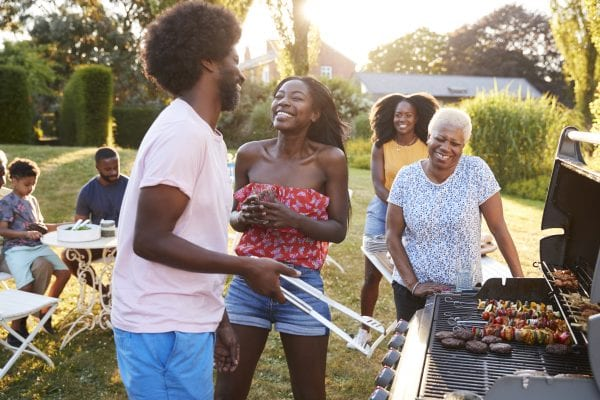 African American couple laughing at a multi generation family barbecue