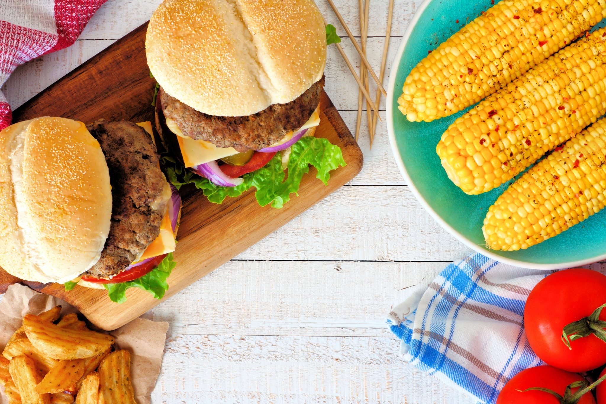 Picnic scene with hamburgers, corn on the cob and potato wedges. Top view over a white wood background.