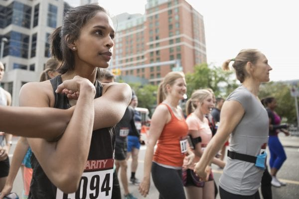 Focused female runner stretching arm on urban street