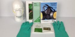 Image of training manuals, green gloves, face mask and other documents.
