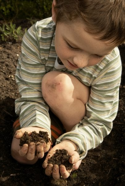 Boy crouching, holding dirt in hands, high angle view