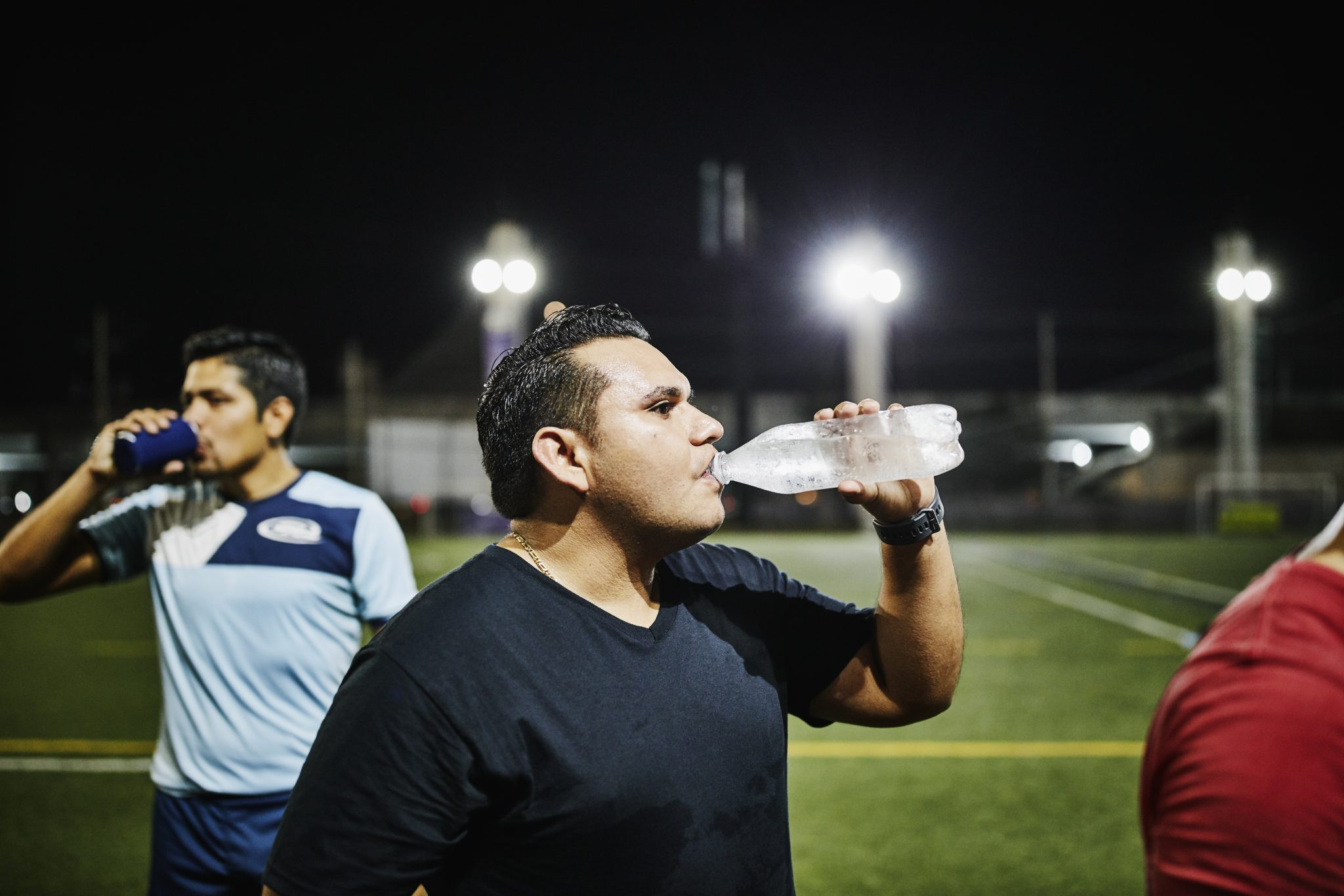 Male soccer player drinking water after nighttime game with friends