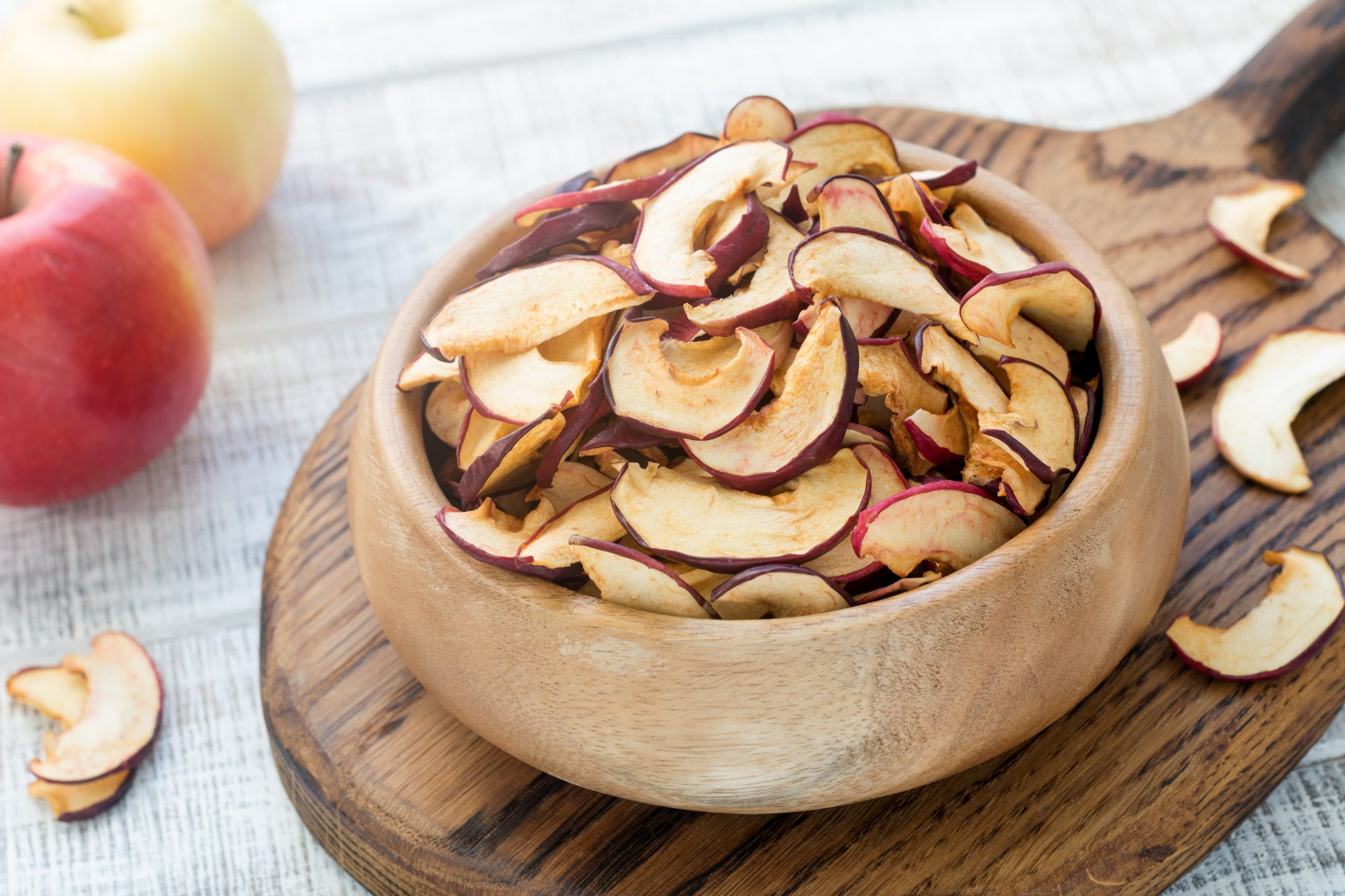 Homemade dried apples or apple chips in a wooden bowl, closeup view